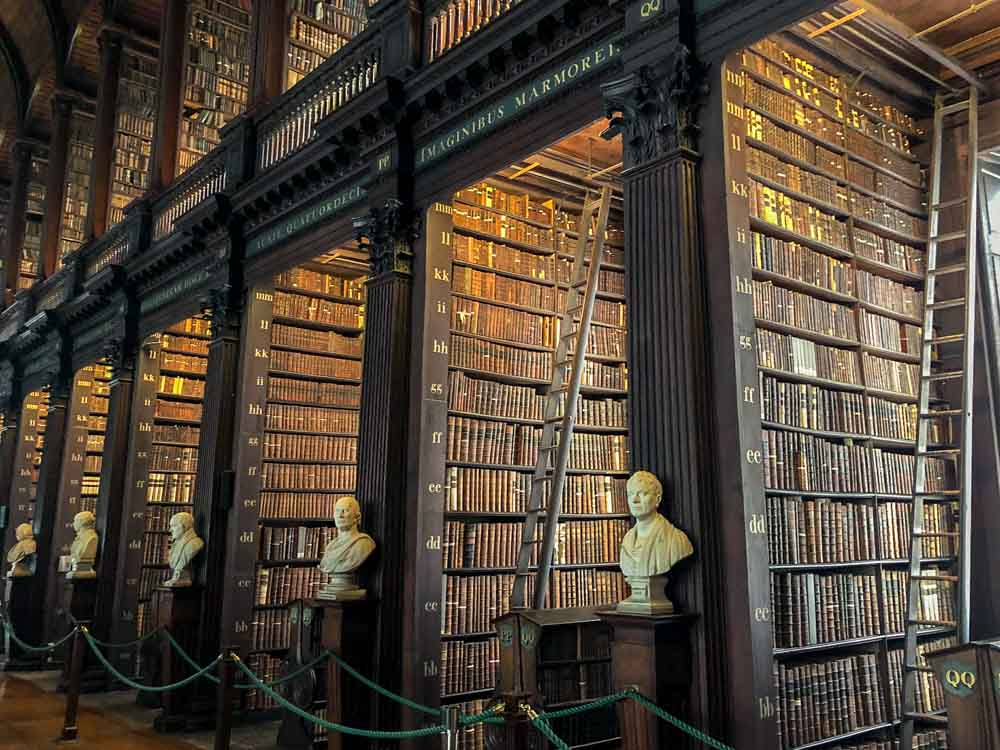 Dublin Trinity College Long Room library. Shelves of books and statues
