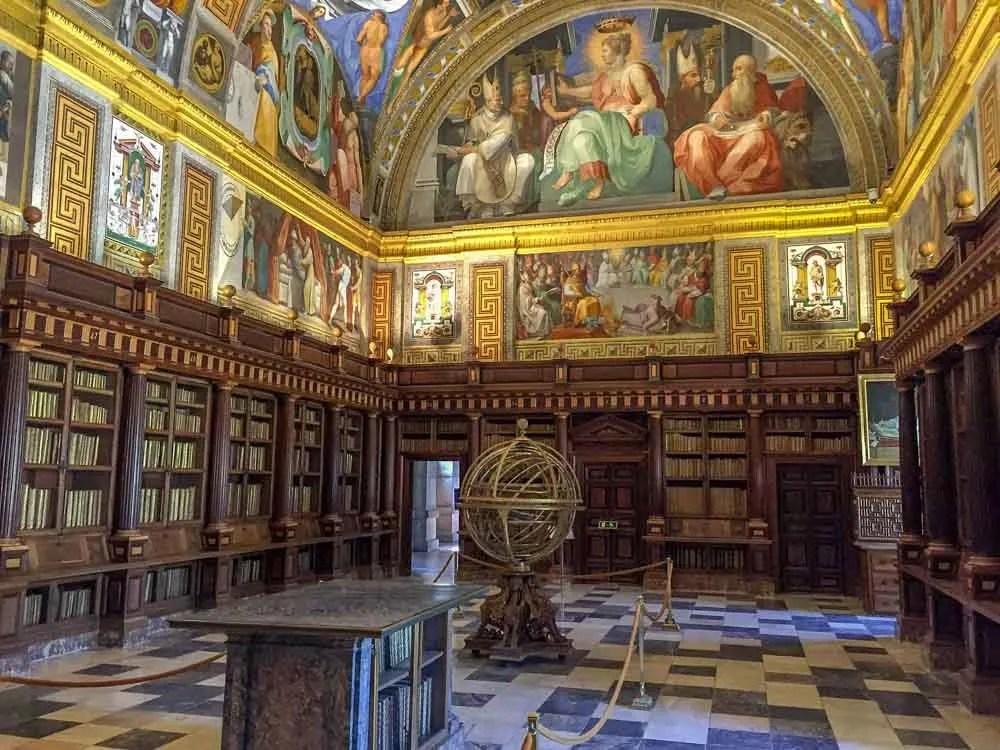 El Escorial library in Spain. Globe sculpture, bookshelves and murals