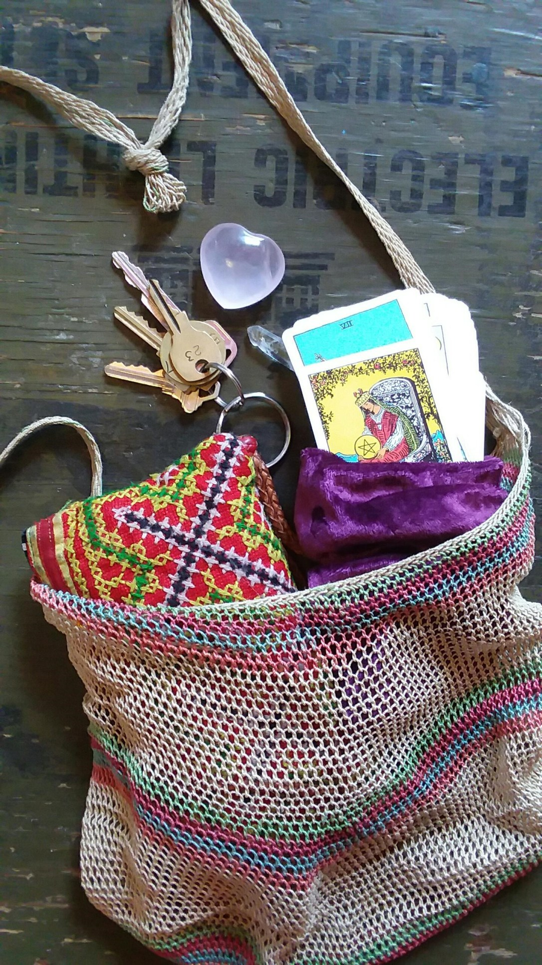 Tarot cards in a purple velvet pouch in a purse and a heart-shaped crystal.