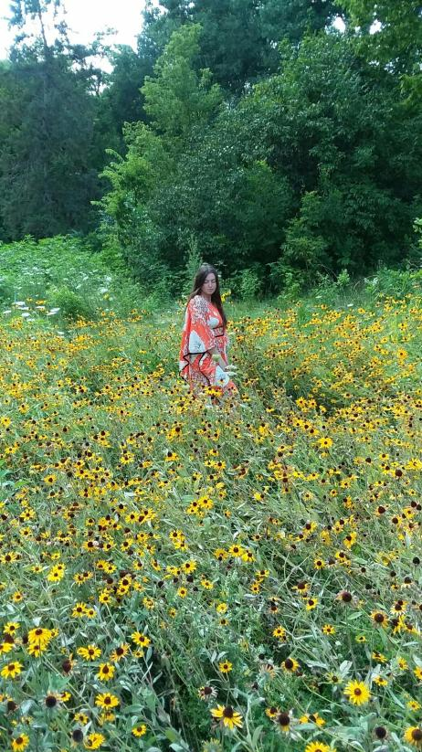 bohemian witch in a field of yellow coneflowers