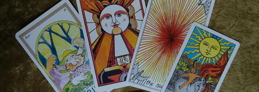 four sun cards from different tarot decks fanned out for summer solstice