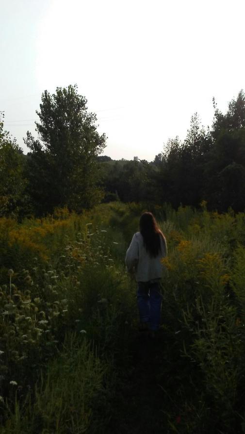 woman walking away through a path in a flowering meadow