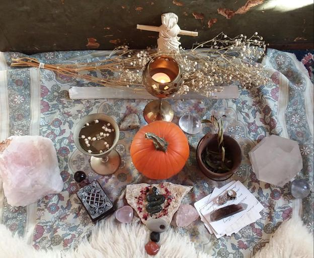 witch's ancestor altar set with stones, crystals, letters, potions, candle, pumpkin, poppet