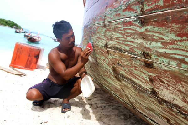 7. A sea gypsy fixes his boat on Lipe Island in the Tarutao marine national park. Sea gyysy rely on fishery which could be destroyed by mega project