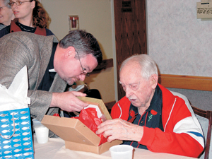 On his 100th birthday, Dillard Wilcox opens a gift from Concordia Theological Seminarian Robert Hauter.