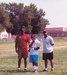 Coach Roosevelt Norfleet talks to receiver Coach Mike Dies and Juan Gorman on a Thursday afternoon workout. photo by rls