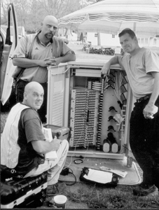 Supervisor Chris Garry (left) and crewmember Chris Mathis and Alex Tipps (right) work on fiber optics splicing at a new terminal on Allegany Avenue on May 6, 2005. They explained that they may be on the job in Fort Wayne for more than a year.