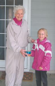 Brownie Girl Scout Ethel Troop 720 delivers nut order to Mrs. Elena Spuller.