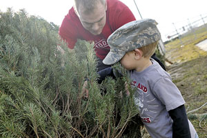 122nd Fighter Wing recruit Michael Streeter and son Abraham inspect Christmas trees for sale at the 122nd Fighter Wing's Historical Air Park, Baer Field Heritage Park.