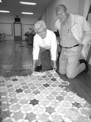 Ida and Morris Willett examine the scrap fabrics used by his mother Thelma to create a partial quilt top while awaiting his birth.