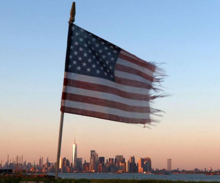 BAYONNE, NJ - MAY 3: A wind blown American flag at the Tear Drop 9/11 Memorial flies over the skyline of New York City as the sun sets on May 3, 2020 in Bayonne, New Jersey. (Photo by Gary Hershorn/Getty Images)