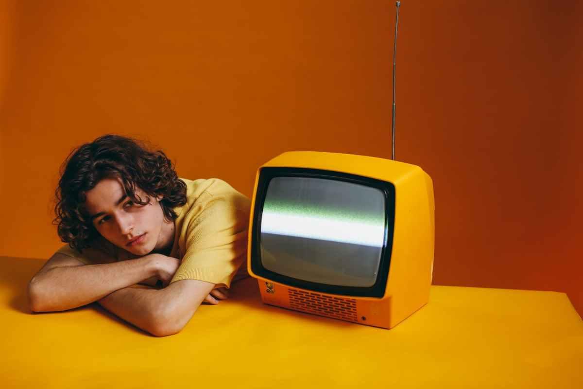 guy in yellow shirt sitting beside a yellow classic tv