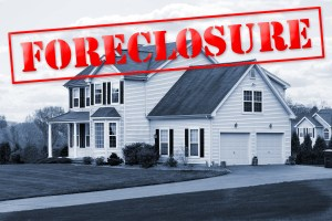 A foreclosed house with a red foreclosure stamp running along the top of the picture.