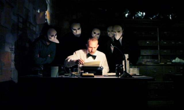 A picture of Sleep No More - an actor sits at a desk in shirtsleeves and a bowtie, examining a sheet of paper sitting in a typewriter. A desklamp illuminates his face. Behind him, in darkness, several masked figures crowd, peering at him, or over his shoulder - the audience of this interactive play.