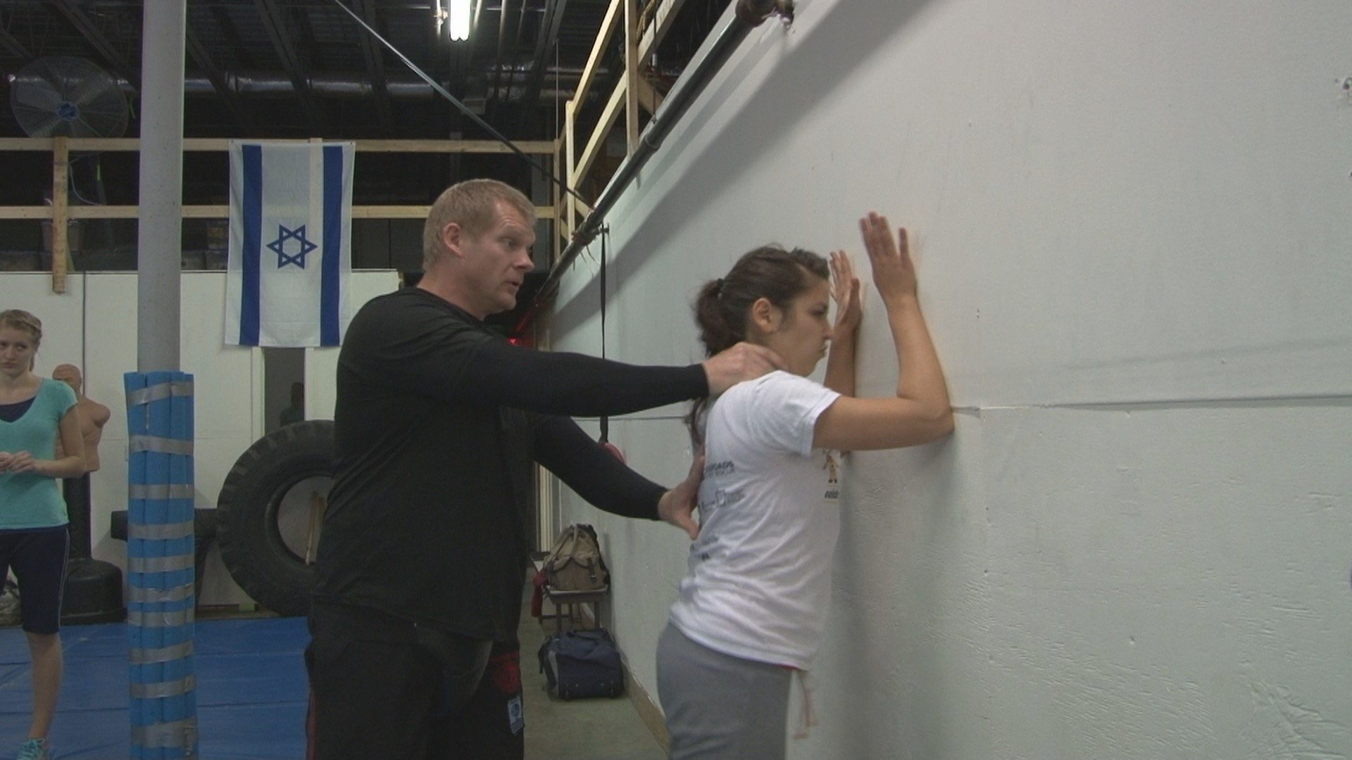 Krav Maga instructor, John Woods, teaches a student how to escape an attack.