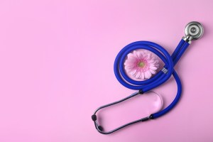 stethoscope and pink flower on pink background - gynecology concept