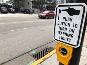 "A sign reading ""push button to turn on warning lights"" mounted above a button on a street light."