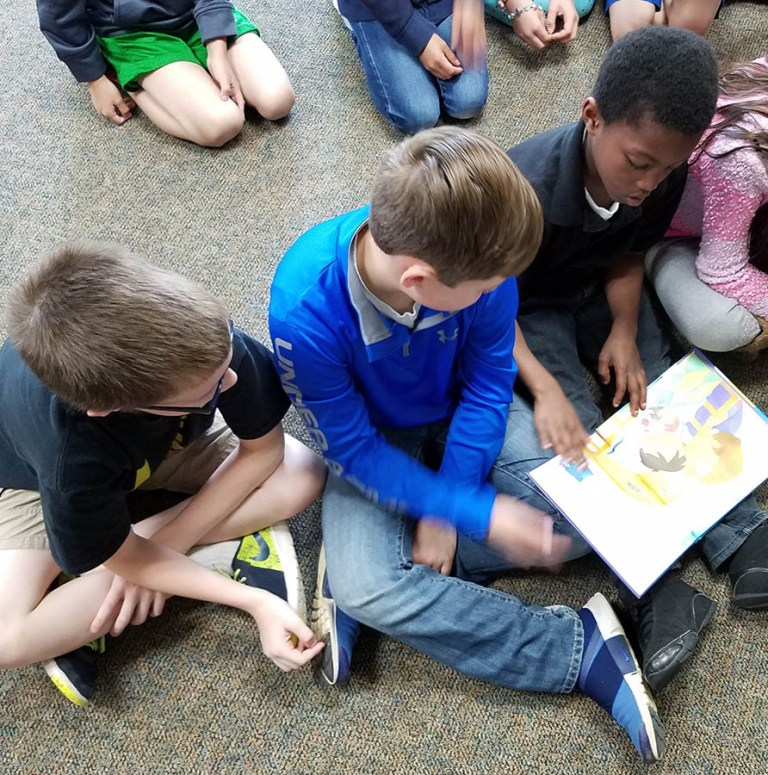 Kids hold a braille book on their lap and explore it