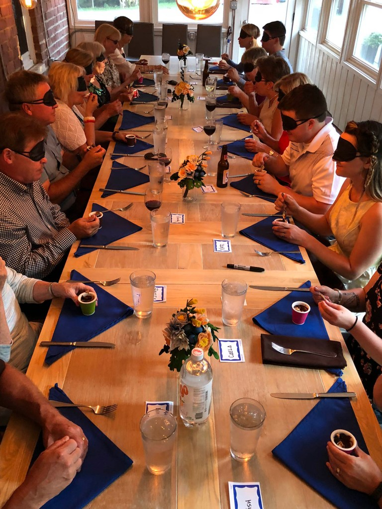 A group of people eat dinner at a long table - all are wearing blindfolds
