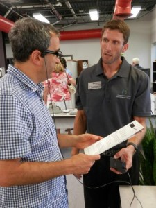 Brent Prezentka, Sharper Vision Store manager (on right) shows a customer how to use the OrCam glasses.