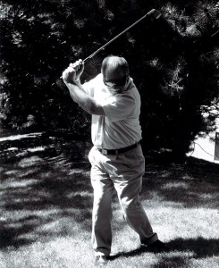 A black and white photo of a man golfing while wearing sunglasses.