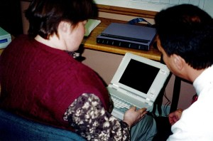 A woman holds a computer device in her lap while a man talks to her.
