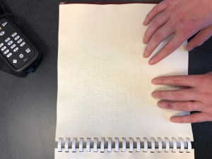 Two hands reading brailled text of a recipe in a cookbook. A black Trek reader is also on the table.