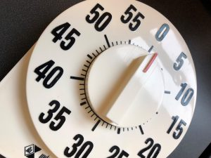 A close-up photo of a black and white kitchen timer.