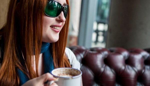 A woman holds a mug of hot chocolate.