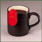 A Liquid Level Indicator hangs on the edge of a coffee mug.