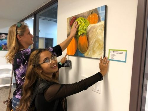 A woman feels a painting while a girl with thick glasses holds the painting steady on the wall.