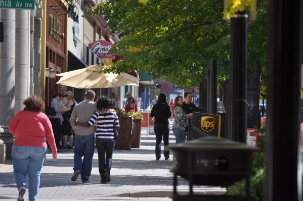 A city sidewalk with people strolling and trees.