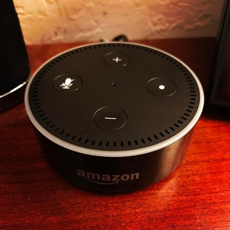 An Amazon Echo sits on a wooden surface.