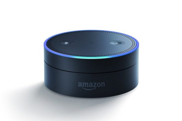 An Amazon Echo Dot sits with its blue ring lit up.