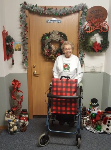 A woman stands with a walker surrounded by Christmas decorations.
