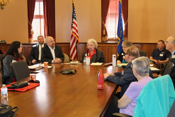 A group of people sit around a table in the Wisconsin state capitol.