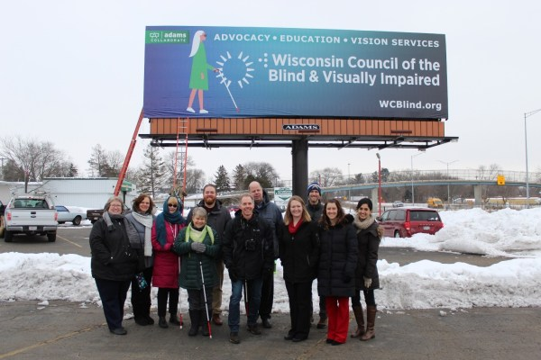 Eleven people stand outside with a billboard behind.