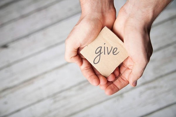 Two Hands holding a small sign that says give.