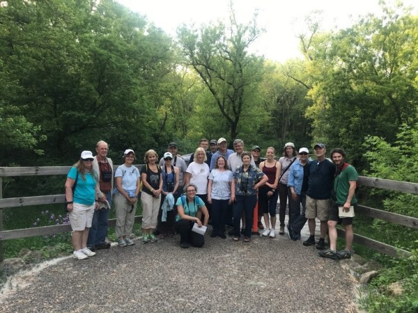 A group of 20 people stands outside on a nature trail.