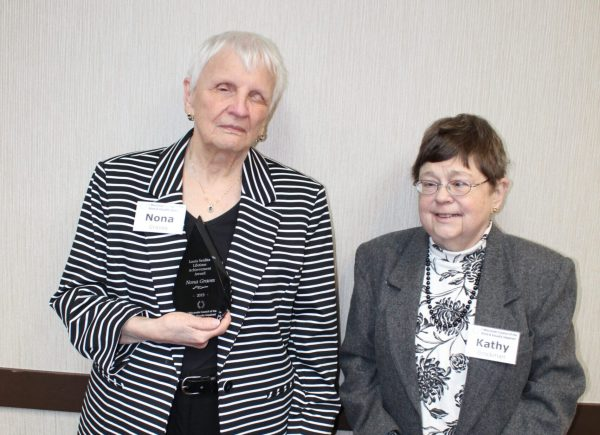 Two woman standing, one holding an award.