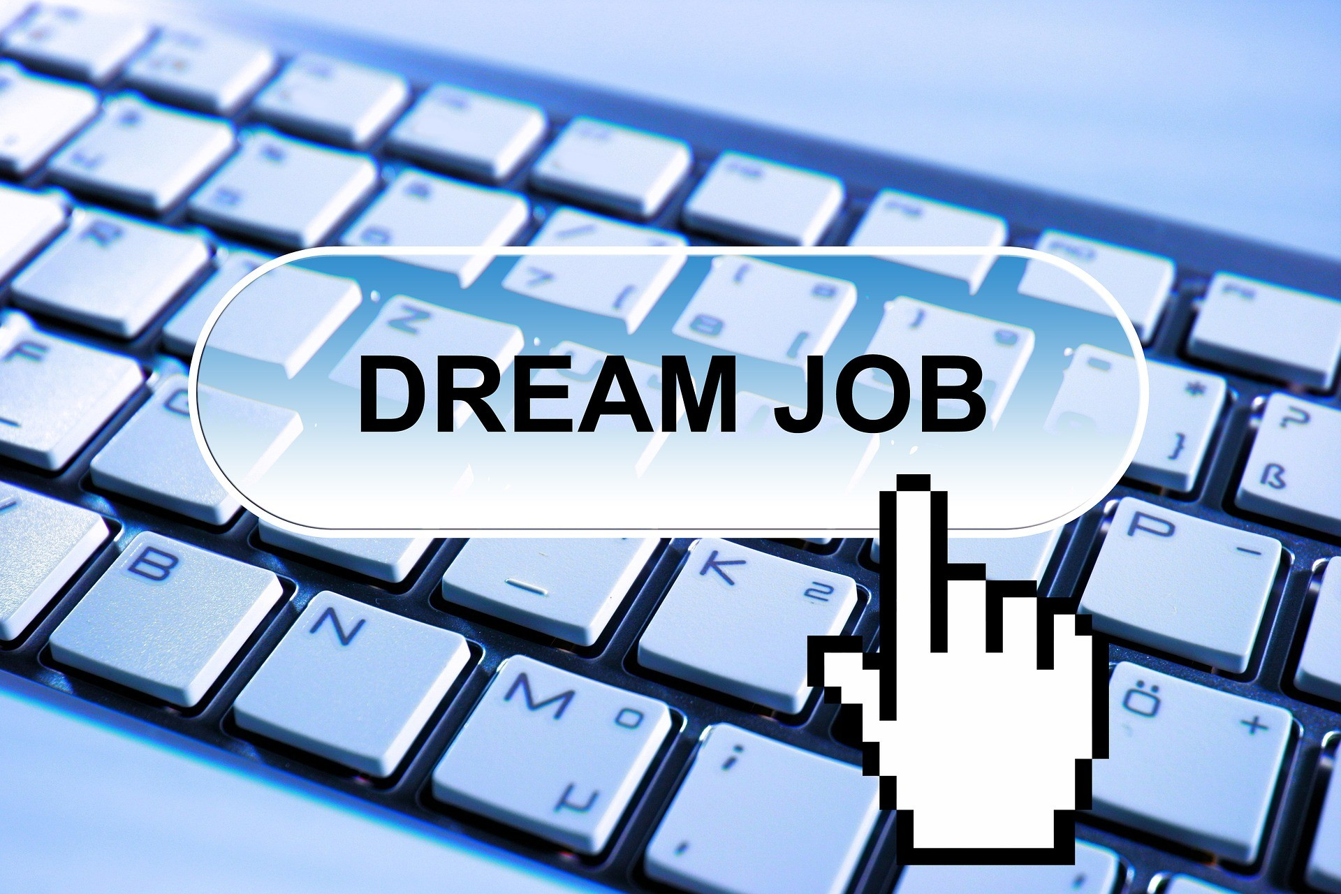 Hand icon pointing to the words dream job with keyboard in the background