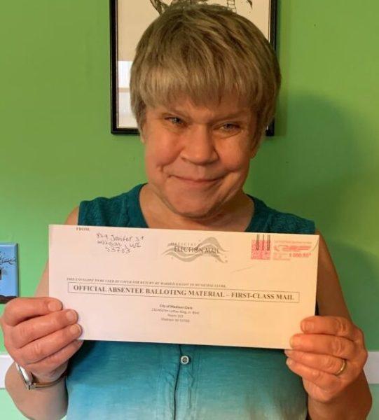 A woman holds up an absentee ballot envelope.