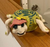 A turtle wearing a pink hat with a light green shell with dark green accents.