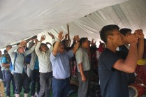 Gathering under the tarps to worship together