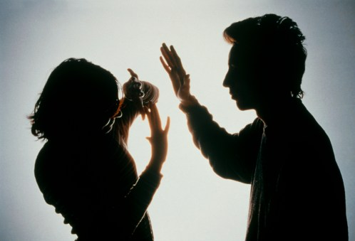 MODEL RELEASED. Domestic violence. Silhouette of a woman protecting herself from a blow from her partner by holding her arms in front of her face.