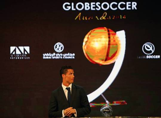 "3Real Madrid's Portuguese football player Cristiano Ronaldo stands on the podium as he awaits to receive his ""Best Player of the Year"" award during the Globe Soccer Awards Ceremony at the end of the 9th International Sports Conference on December 29, 2014 in Dubai.  AFP PHOTO / MARWAN NAAMANI        (Photo credit should read MARWAN NAAMANI/AFP via Getty Images)"