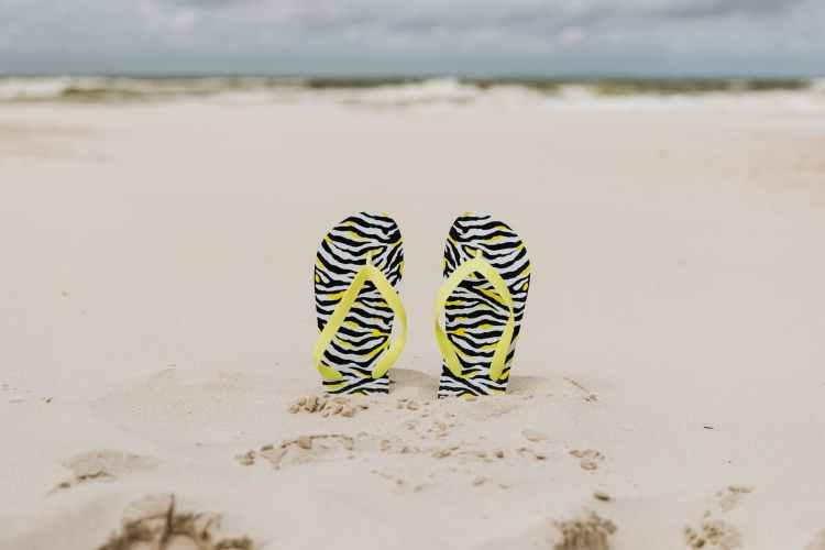 black and green stripe flip flops on white sand