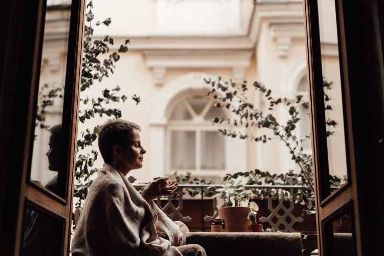 concentrated woman with aromatic coffee on balcony at home