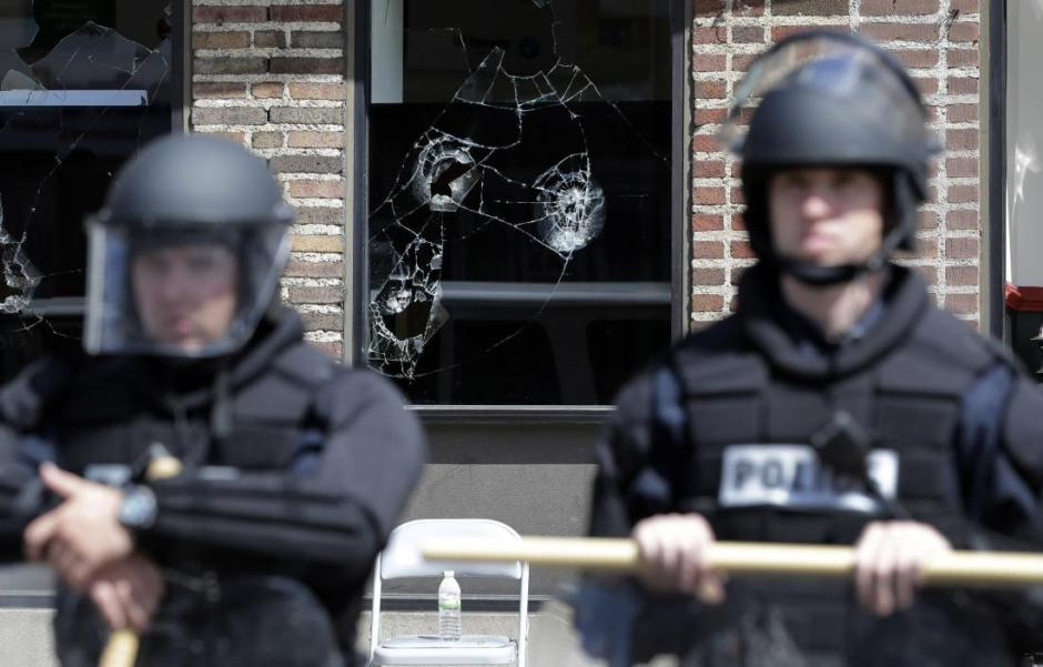 Broken store windows remain as members of the Anne Arundel County Police guard the intersection of North Avenue and Pennsylvania Avenue, Wednesday, April 29, 2015, in Baltimore. Schools reopened across the city and tensions seemed to ease Wednesday after Baltimore made it through the first night of its curfew without the widespread violence many had feared. People in Baltimore have been angry over the police-custody death of Freddie Gray.  (AP Photo/Patrick Semansky)