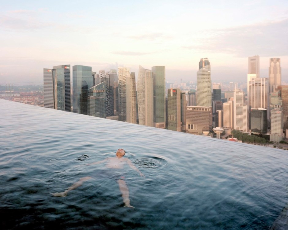 "A man floats in the 57th-floor swimming pool of the Marina Bay Sands Hotel, with the skyline of ""Central,"" the Singapore financial district, behind him. Singapore"